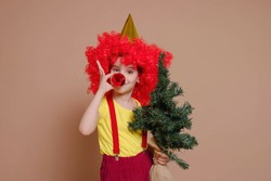 Funny clown girl in a red wig and with a nose made of a Christmas ball-toy holds a Christmas tree isolated against the background of a Set Sail Champagne flower. Holidays, circus concept.
