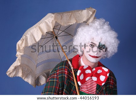 funny clown with white hair and umbrella on blue background - stock photo