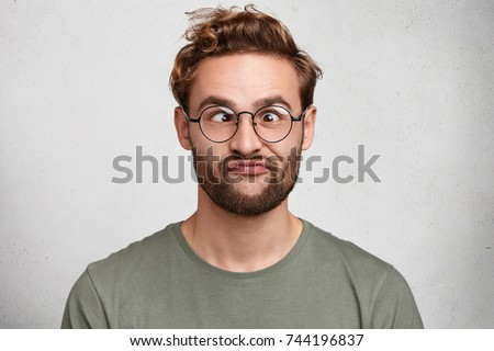 Funny comic man crosses eyes, pouts lips, makes grimace, foolishes after all day studying. Clueless male nerd with awkward expression has fun alone, plays fool, isolated over white background Foto d'archivio ©