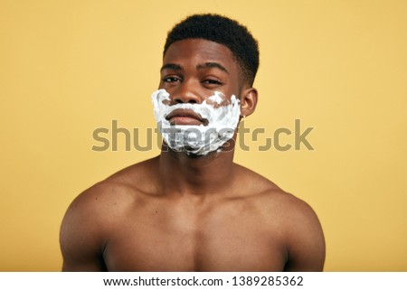 funny comical man making faces, isoltaed yellow background,guy with pleasant appearance, have shaving foam on faces