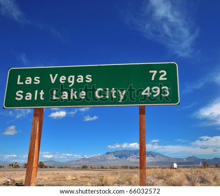 Funny contrast of cities on a road sign.