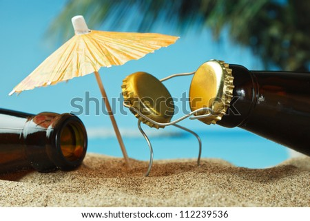 funny cork and bottle on a sandy beach - stock photo