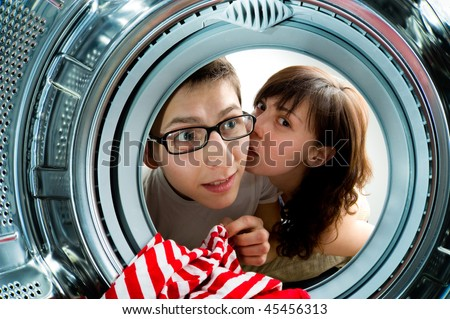 Funny couple loading clothes to washing machine. From inside the washing machine view.