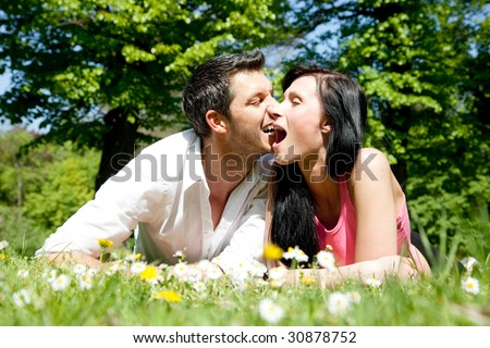 Funny couple lying in park green grass
