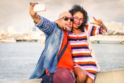 Funny couple taking selfie using cell phone at pier with ocean background - Young traveling people having fun with mobile phone  doing self photo - Concept of travel and joyful lifestyle at sunset