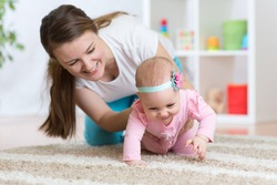Funny crawling baby girl with mother