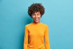 Funny crazy comic Afro American woman makes grimace and crosses eyes plays fool has fun alone sticks out tongue wears casual jumper poses against blue background. Human face expressions concept