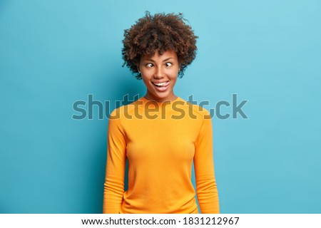 Funny crazy comic Afro American woman makes grimace and crosses eyes plays fool has fun alone sticks out tongue wears casual jumper poses against blue background. Human face expressions concept Stockfoto ©