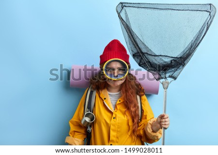 funny crazy ginger tourist has prepared for travel. madness, craziness. close up portrait, hobby, lifestyle, interets,isolated blue background, studio shot