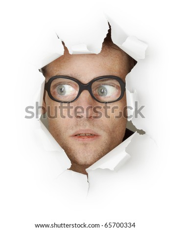 Funny crazy man face in old eyeglasses looking out of the hole isolated on white background