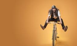 Funny crazy man riding a bike, on studio background