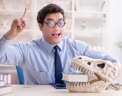 Funny crazy professor studying dinosaur skeleton