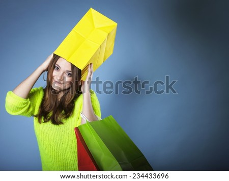 Funny crazy woman bright vivid colour sweater with paper shopping bag on head blue background. Sales and discounts concept.