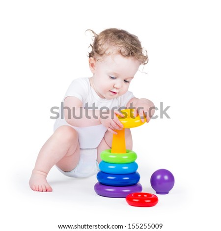 Funny curly baby girl playing with a colorful pyramid on white background