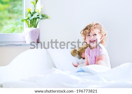 Funny curly toddler girl waking up on a early sunny morning in a white bedroom with window playing with her toys