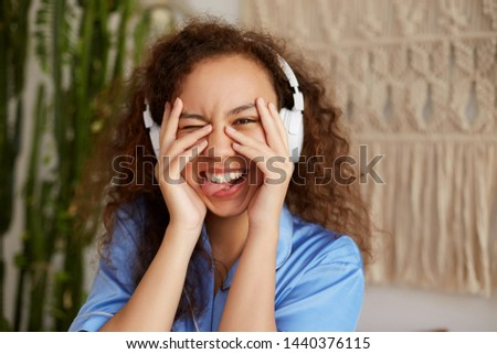 Funny curly young young woman, broadly smiles and listening favorite song in headphones, enjoying the music and Sundays morning, looks through his fingers and shows tongue.