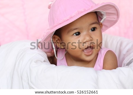 Stock Photo Funny cute baby with big black eyes wearing a hat and smile