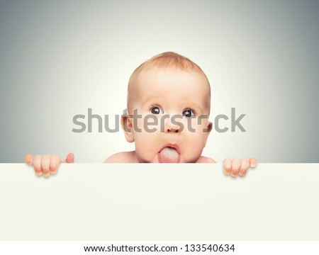funny cute baby with white blank banner in hand isolated on a gray background