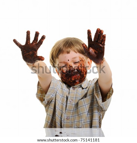 funny, cute dirty and bedaubed boy - chocolate on hands and face