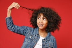 Funny cute little african american kid girl 12-13 years old wearing casual denim jacket hold curl hair isolated on bright red color background children studio portrait. Childhood lifestyle concept