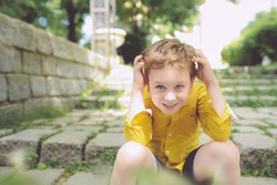 funny cute preschool boy in a yellow shirt and a shaggy hairstyle holds his head, smiles and sits on a stone staircase with green grass on the street
