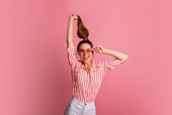 Funny  cute woman  holding hairs up on pink background. Happy female in striped blouse and white jeans posing in studio.
