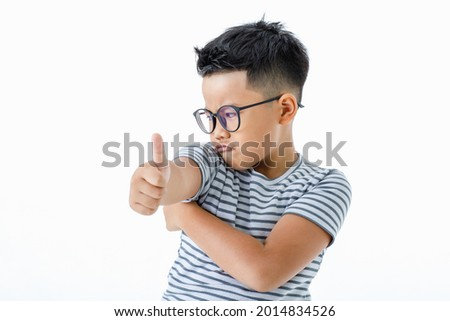 Funny cutout portrait of pity young Asian boy wearing glasses and horizontal striped shirt disappointed on unwanted thing by turning away with left arm crossed and thumb up as disagree sign Stock photo ©