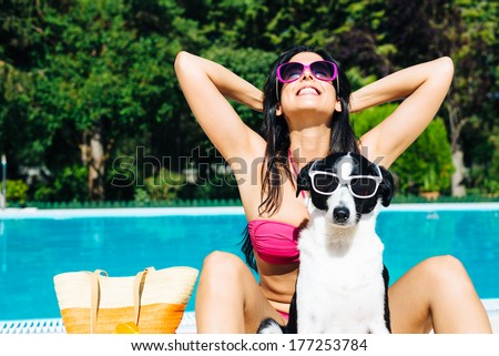 Funny dog and woman on summer vacation at swimming pool.