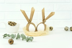 Funny Easter eggs lie in a straw nest as a decoration for happy hollidays