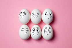 Funny Easter eggs with facial expressions. Eggs with different faces on pink background.