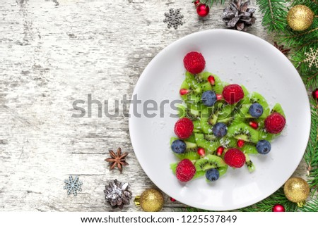 Funny edible christmas tree made from fruits and berries with fir tree and decorations. Christmas breakfast idea for kids. Christmas and New Year food background. top view with copy space #1225537849