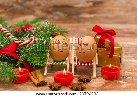 funny eggs on a beach chairs, Christmas tree, mandarine, gift and candles.  christmas background theme