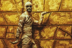 Funny emotional Halloween mummy dances by a wall with ancient Egyptian hieroglyphs. Halloween party. Ancient Egyptian mythology.