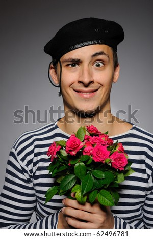 Funny emotional romantic sailor man holding rose flowers prepared for a date - stock photo