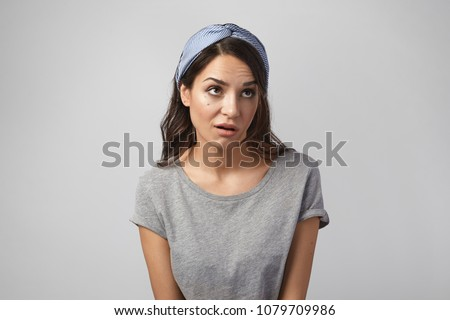 Funny emotional young Caucasian woman wearing gray top and headscarf grimacing, rolling her eyes, expressing annoyance, pissed off or bored with something. Human emotions, reaction and attitude