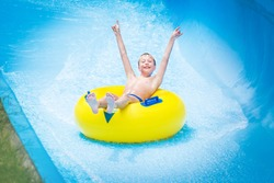 Funny excited child enjoying summer vacation in water park riding yellow float laughing.
