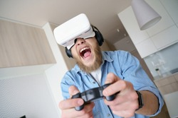 Funny excited young hipster man gamer wearing vr glasses headset holding joystick controller playing video game at home alone, virtual reality 3d futuristic gaming simulator experience concept.