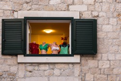 Funny exposition of bras and underclothes in old window with wooden shutters.