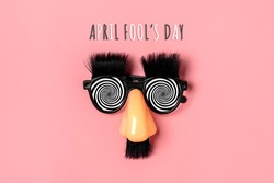 funny face - fake eyeglasses, nose and mustache on pink background Happy fools day  concept  1st April party Holiday card