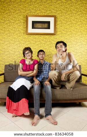 funny family, father, mother and son pose funny on a couch in yellow living room.