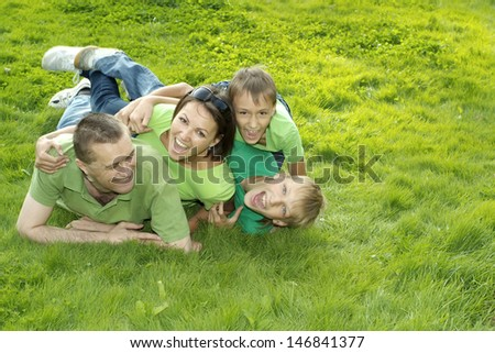 funny family of four lying on the grass in the park