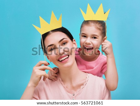 Funny family on a background of bright blue wall. Mother and her daughter girl with a paper accessories. Mom and child are holding crown on stick.