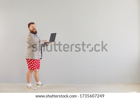 Funny fat man in a blue shirt and red shorts standing working online using a laptop on a gray background.
