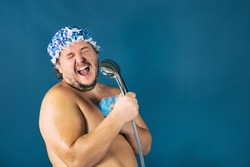 Funny fat man in blue cap sing in the shower. Fun and cleanliness