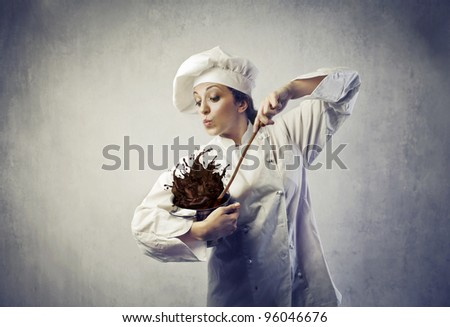 funny female cook mixing some chocolate dough spilling from a pot