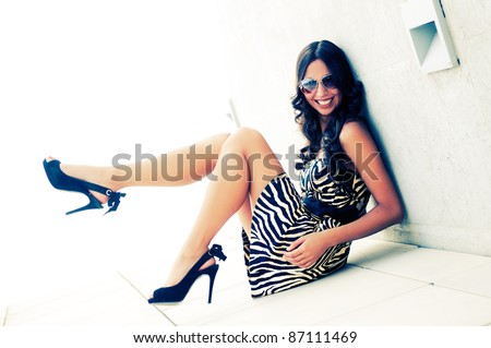 Funny female model at fashion with high heels sitting on the floor