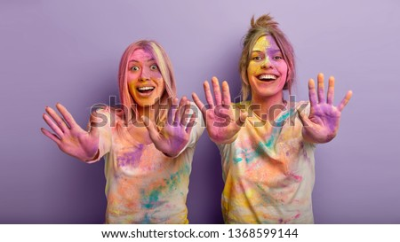 Funny Festival of Colors. Joyful women with splattered clothes, show multicolored palms, have outstretched hands, have fun together at Holi holiday, isolated over purple background. Festive energy