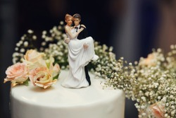 Funny figurines suite at a luxury wedding white cake decorated with fresh flowers.