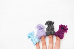 Funny finger people family couple smiling with red cheeks wearing knitted woolen hats under snow