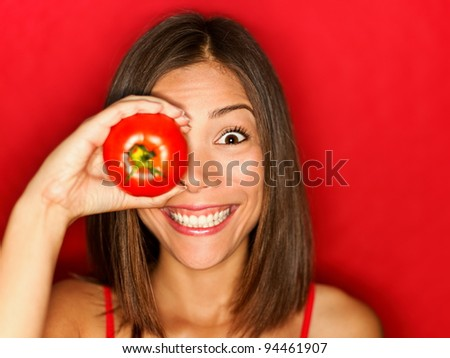Funny food woman with red tomato smiling happy. Healthy eating and vegetables concept photo with fresh cute multiracial mixed race Asian Caucasian female model on red background.